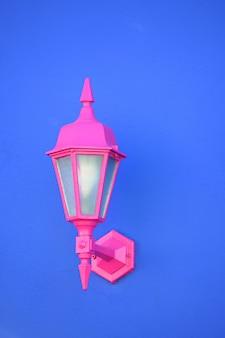 Tiro vertical de uma lâmpada de arandela rosa anexada a uma parede azul