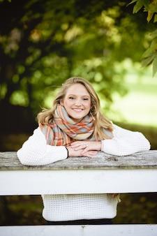 Tiro vertical de uma linda mulher loira sorridente, inclinando-se sobre uma borda de madeira