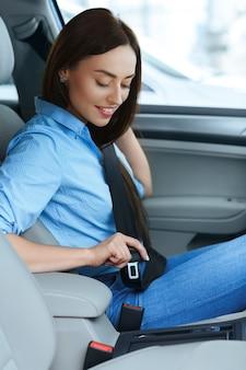 Tiro vertical de uma linda mulher sentada em um carro, colocando o cinto de segurança sorrindo alegremente