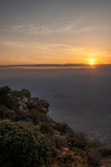 Tiro vertical de uma montanha coberta de árvores e o pôr do sol capturado no quênia, nairobi, samburu