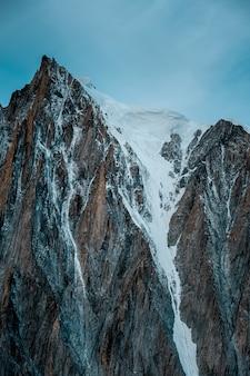 Tiro vertical de uma montanha de neve com um céu claro ao fundo