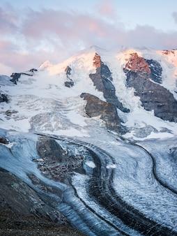 Tiro vertical de uma montanha de neve sob um céu nublado