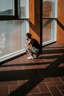 Tiro vertical de uma mulher agachada, olhando pela janela