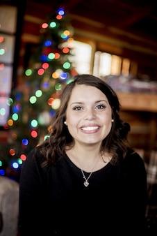 Tiro vertical de uma mulher branca sorrindo na frente de um alegre festivo