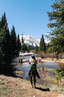Tiro vertical de uma mulher com mochila em pé perto da água e árvores com uma montanha no fundo