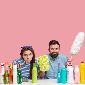 Tiro vertical de uma mulher descontente surpresa e trabalhadores de serviço do homem usam vários detergentes, homem barbudo segura esfregão e espanador de pp, sente-se à mesa branca, ocupado limpando a casa. higiene e limpeza