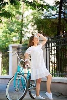 Tiro vertical de uma mulher feliz, descansando depois de andar de bicicleta em pé perto de sua bicicleta, olhando para longe