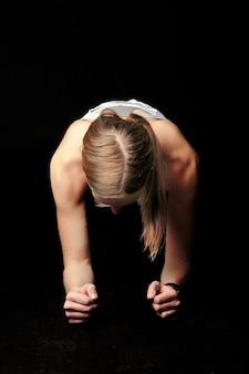 Tiro vertical de uma mulher na hora do treino em uma parede preta