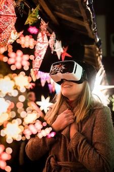 Tiro vertical de uma mulher que aprecia a atmosfera imaginária com óculos de realidade virtual