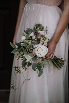 Tiro vertical de uma noiva usando vestido de noiva, segurando um buquê de flores