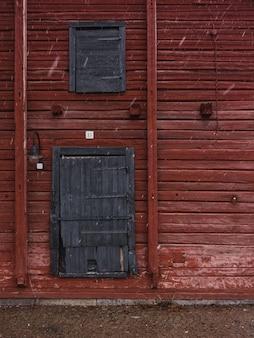 Tiro vertical de uma parede de madeira vermelha com portas de madeira cinza no inverno