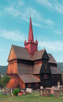 Tiro vertical de uma paróquia de concreta marrom sob o lindo céu nublado na noruega