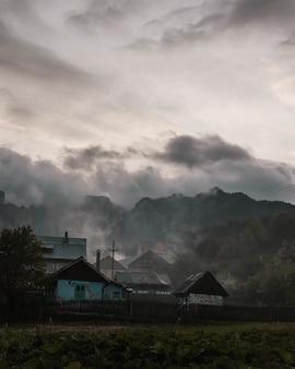 Tiro vertical de uma pequena vila com incríveis montanhas rochosas, rodeadas por nevoeiro e nuvens naturais