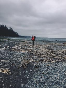 Tiro vertical de uma pessoa em pé em uma praia rochosa ao lado do oceano