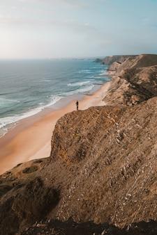 Tiro vertical de uma pessoa em um penhasco, olhando para o belo oceano no algarve, portugal