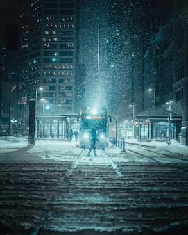 Tiro vertical de uma pessoa na frente de um trem em uma estrada com neve