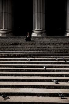 Tiro vertical de uma pessoa sentada na escada perto de colunas