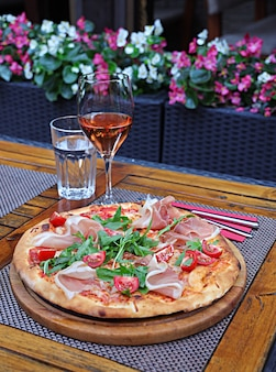 Tiro vertical de uma pizza com presunto e tomate em uma placa de madeira em cima da mesa com bebidas