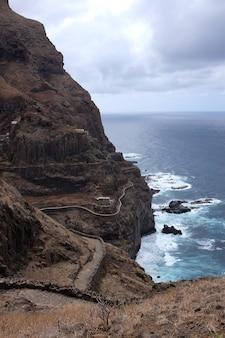 Tiro vertical de uma rocha à beira-mar sob o céu sombrio