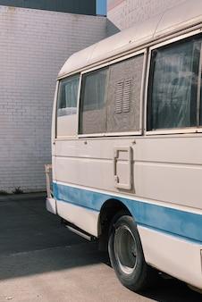 Tiro vertical de uma van branca e azul estacionada do lado de fora durante o dia