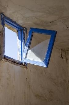Tiro vertical de uma velha janela azul rústica prestes a quebrar e cair na sala em ruínas