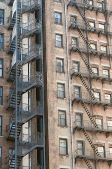 Tiro vertical de velhos prédios de apartamentos de pedra com escadas de saída de incêndio nos lados