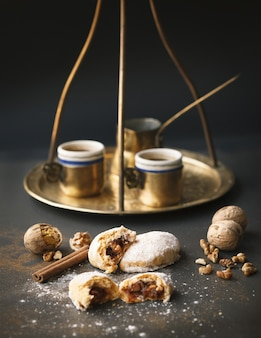 Tiro vertical de xícaras de café douradas e um jazzve com biscoitos e nozes em uma superfície preta