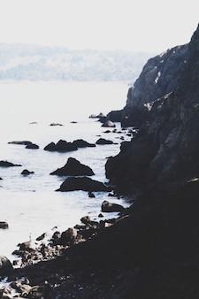 Tiro vertical do belo mar com altas falésias rochosas à esquerda