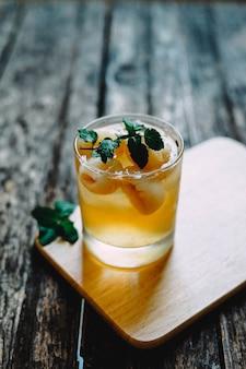 Tiro vertical do close up de um cocktail alcoólico em um copo na montanha russa de madeira com uma folha da hortelã na parte superior