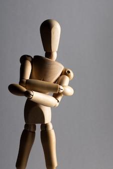 Tiro vertical do close up de uma boneca de madeira pose com os braços cruzados em pé na sombra