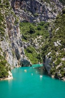 Tiro vertical do corpo de água entre penhascos rochosos e montanhas