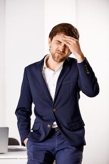 Tiro vertical do empresário sentir burnout, toque na testa e estrabismo, sofrendo dor de cabeça, enxaqueca dolorosa no escritório do trabalho