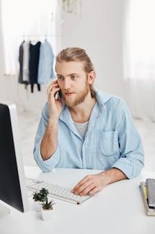 Tiro vertical do freelancer bonito caucasiano com barba e cabelo loiro, verificando informações e digitando texto promocional. empregado masculino olhando agradável tem conversa por telefone com os clientes.
