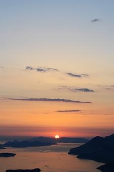 Tiro vertical do horizonte com água e o pôr do sol em um céu azul de tirar o fôlego