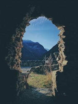 Tiro vertical do interior de uma caverna com uma montanha