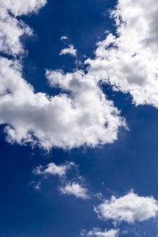 Tiro vertical do lindo céu azul com grandes nuvens brancas de tirar o fôlego