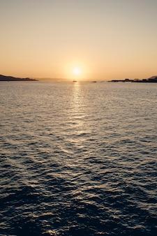 Tiro vertical do mar, refletindo a luz do sol com um lindo céu