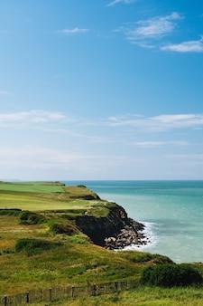 Tiro vertical do penhasco com um campo gramado perto do mar sob um céu azul durante o dia na frança
