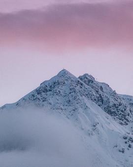 Tiro vertical do pico da montanha coberta de neve sob o céu nublado colorido