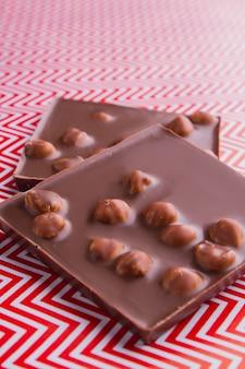 Tiro vertical dois pedaços de barra de chocolate com avelãs