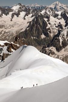 Tiro vertical dos magníficos picos das montanhas cobertas de neve