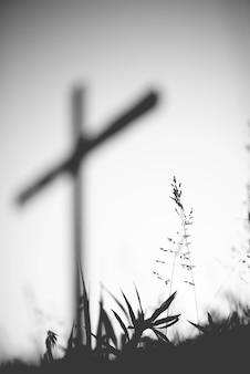 Tiro vertical em escala de cinza de um campo gramado com uma cruz borrada