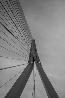 Tiro vertical em escala de cinza de uma ponte suspensa sob o céu nublado