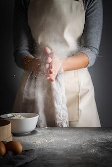 Tiro vertical mulher com farinha nas palmas das mãos