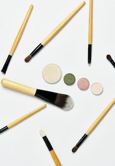 Tiro vertical, pincéis de maquiagem profissionais colocados aleatoriamente, com paleta de sombras nuas simetricamente dispostas, isolada no fundo branco. vista superior, flatlay. o conceito de maquiagem, cosméticos, rosto.