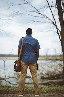 Tiro vertical por trás de um homem vestindo uma bolsa e segurando a bíblia
