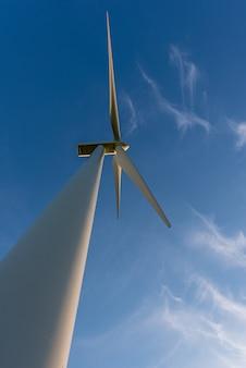 Tiro vertical que olha acima em uma turbina eólica, em um céu azul e em umas nuvens brancas. de meio ambiente