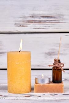 Tiro vertical queimando uma vela amarela com sabão e óleo. backgrond de madeira branca.