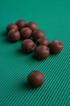 Tiro vertical redondo bombons de chocolate sobre fundo verde. conjunto de vários doces de chocolate marrom.