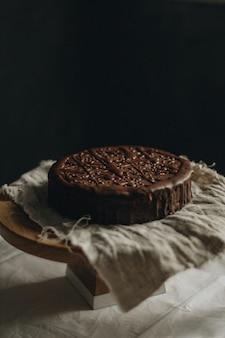 Tiro vertical seletivo closeup de bolo de chocolate em um tecido em uma mesa redonda